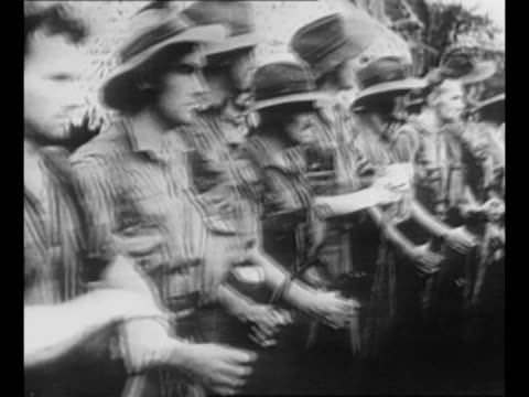 australian soldiers approach as they walk in line on new guinea during world war ii / soldiers walk away, pass other groups of soldiers standing... - the world's end stock videos & royalty-free footage