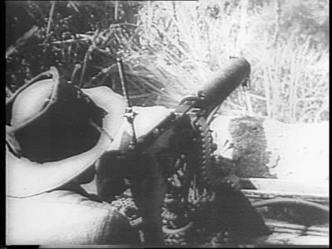 australian soldiers fire machine gun and mortars at japanese sniper nest in trees / snipers return fire / soldier looking through binoculars /... - 煙草製品点の映像素材/bロール