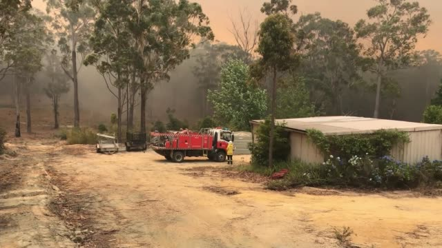 vidéos et rushes de thousands evacuated as wildfires spread; australia: moruya: ext gv helicopter flying over fire dropping retardant on flames tilt down retardant... - kangourou