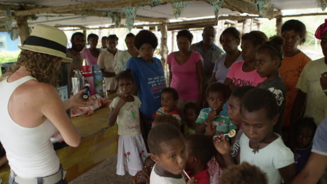 vanuatu - march 31, 2015: australian woman demonstrates water filtration system surrounded by group of locals - wiederaufbau stock-videos und b-roll-filmmaterial