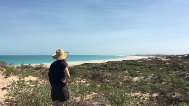vídeos de stock e filmes b-roll de australian woman looking at cable beach in broome western australia - cable