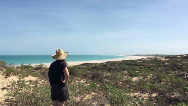 vídeos de stock, filmes e b-roll de australian woman looking at cable beach in broome western australia - cable