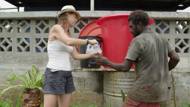vanuatu - march 31, 2015: australian woman shows local man how water filtration system works - charity and relief work stock videos & royalty-free footage