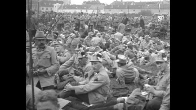 vidéos et rushes de austrian troops standing in street with their rifles stacked in front of them / pan across soldiers sitting in large open field waiting / close shot... - culture autrichienne