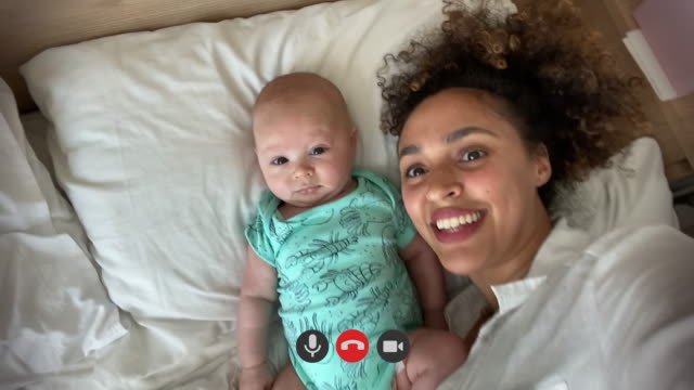 authentic close up of young adult mother and her newborn baby in bed making on video call to father or relatives in bedroom - purity stock videos & royalty-free footage