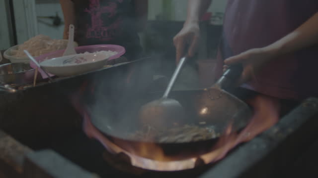 CU SLO MO Authentic cooking over open fire in street kitchen in city at night / Shanghai, China