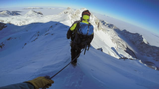 POV Authentic descend of roped mountaineers at daytime