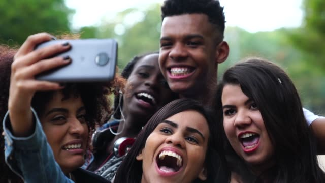 vídeos de stock e filmes b-roll de authentic group of diverse friends taking a selfie at park - brazilian ethnicity