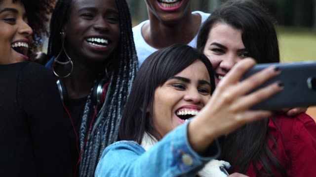 authentic group of diverse friends taking a selfie at park - 18 teen stock videos & royalty-free footage