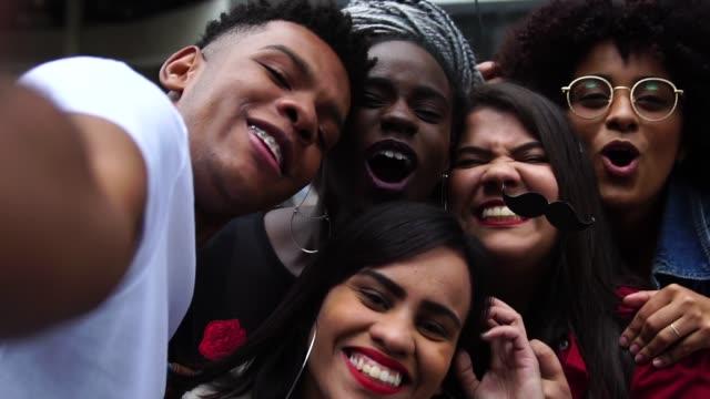vidéos et rushes de authentique groupe de divers amis prenant un selfie - métis