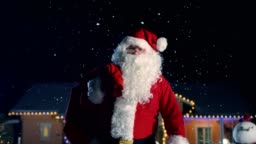 Authentic Santa Claus Carrying Red Bag over the Shoulder, Walks out of the Idyllic House Decorated with Lights and Garlands. Santa Bringing Gifts and Presents. Magical New Year's Eve with Falling Snow.
