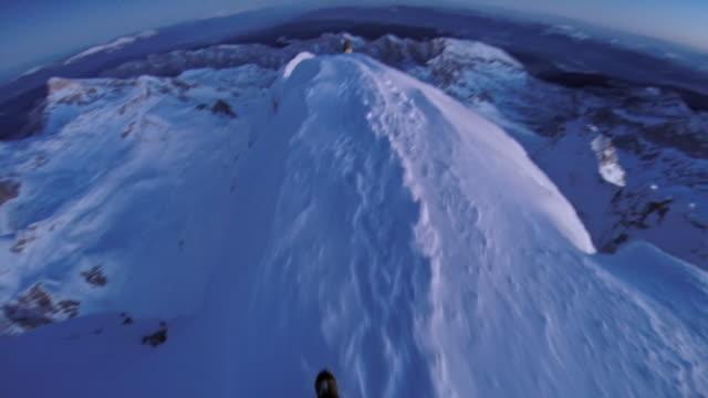 POV Authentic shot of alpinists descending snowy ridge at sunset