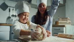 Authentic shot of an young mother and little daughter are having fun to cook and playing with the flour in the kitchen.