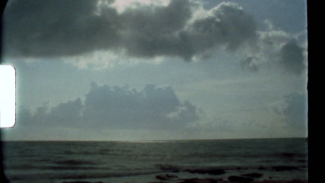 authentic super 8 film of backlit clouds over a tropical beach - 8mm film projector stock videos & royalty-free footage