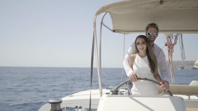 vidéos et rushes de authentic wealth - romantic owner couple steering their catamaran together - embrasser sur la bouche
