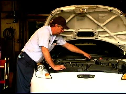 vídeos y material grabado en eventos de stock de auto mechanic and young man by car - encuadre de tres cuartos