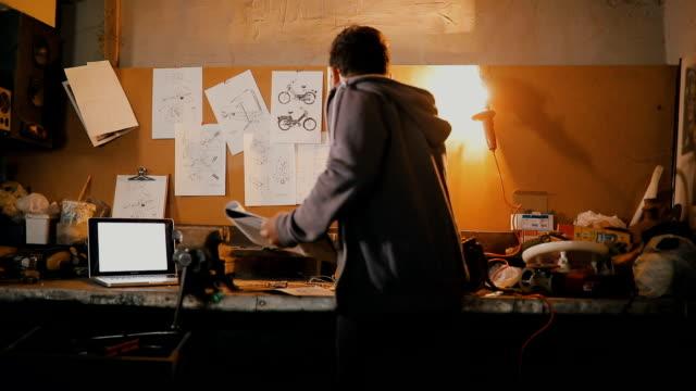 vídeos de stock e filmes b-roll de auto mechanic assembles custom motorcycle in his workshop - peça de máquina