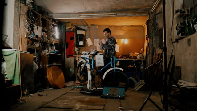 auto mechanic assembles custom motorcycle in his workshop - workshop stock videos & royalty-free footage