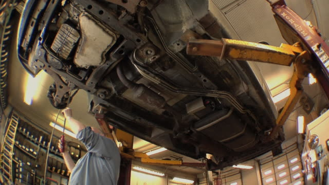 ms auto mechanic checking some key components of vehicle's undercarriage at auto repair shop / chelsea, michigan, usa - hydraulics stock videos and b-roll footage