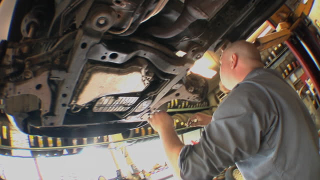 CU TS Auto mechanic checking some key components of vehicle's undercarriage at auto repair shop / Chelsea, Michigan, USA