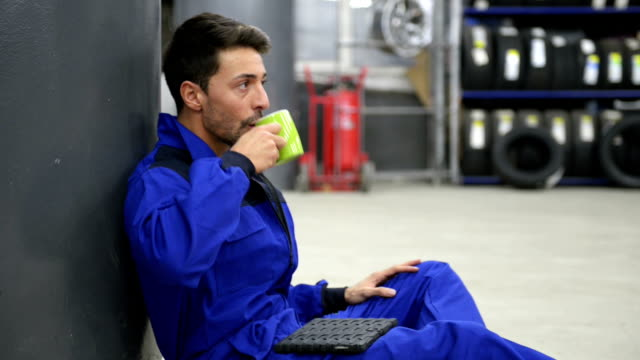 Auto mechanic having a coffee break