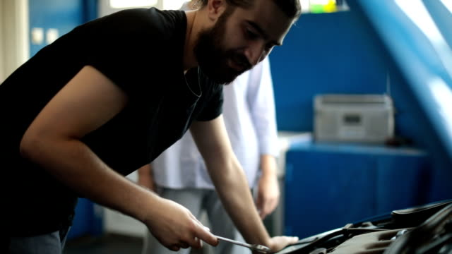 auto mechanic helping customer - offrire un servizio video stock e b–roll