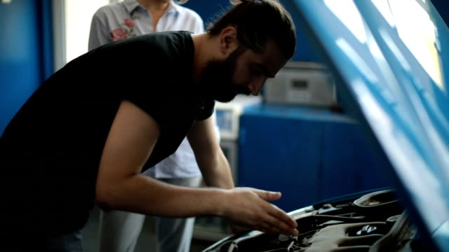 Auto mechanic helping customer