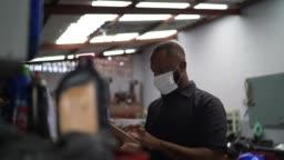 Auto mechanic man walking using digital tablet at car repair shop