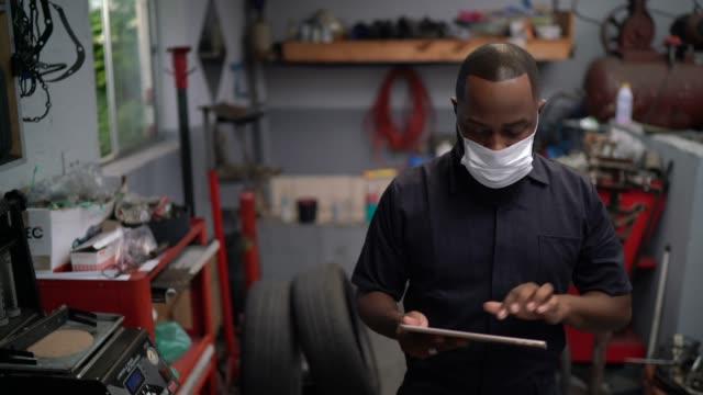 auto mechanic man walking using digital tablet at car repair shop - laboratorio riparazioni video stock e b–roll
