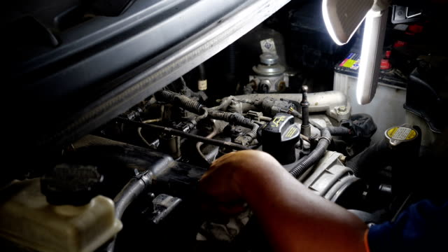 自動車サービスセンターで働くランプを持つ自動車整備士の男。 - 測定器点の映像素材/bロール
