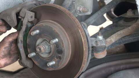 自動車整備士修理ディスクブレーキ - ディスク点の映像素材/bロール