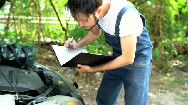 Auto mechanic repairing car by checking item list on his hand.