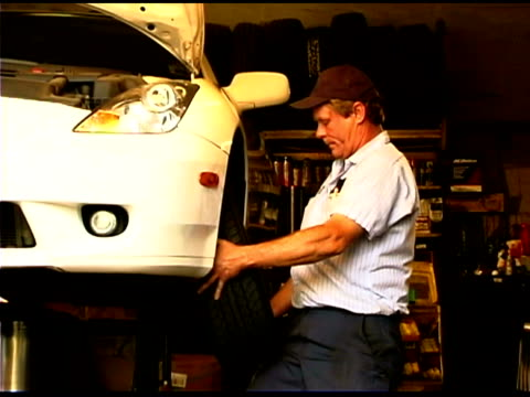 stockvideo's en b-roll-footage met auto mechanic repairing car - alleen één oudere man