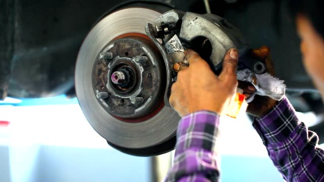 auto mechanic  repairing the disc brake underneath the car lift - calliper stock videos and b-roll footage