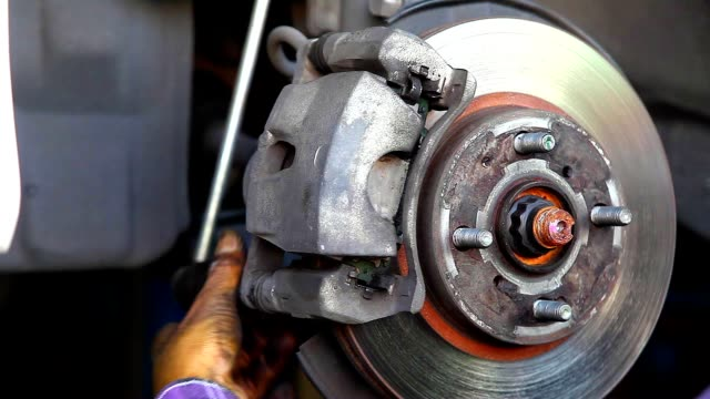 auto mechanic  repairing the disc brake underneath the car lift - wrench stock videos and b-roll footage