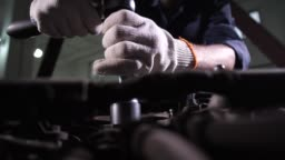 Auto mechanic replacing car oil filter during work