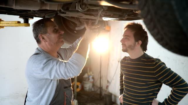 automechaniker gespräch mit dem auto eigentümer - automobilindustrie stock-videos und b-roll-filmmaterial