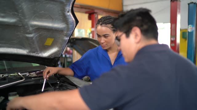 auto mechanic woman doing a customer checklist in auto repair shop - laboratorio riparazioni video stock e b–roll