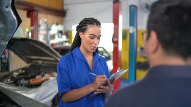 auto mechanic woman doing a customer checklist in auto repair shop - mechanic stock videos & royalty-free footage