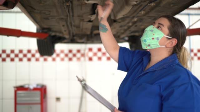 vídeos de stock, filmes e b-roll de mulher mecânica de automóveis fazendo checklist na oficina de reparos de automóveis - indústria automobilística