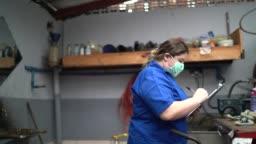 Auto mechanic woman walking and doing checklist at car repair shop
