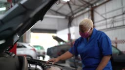 Auto mechanic woman working at car repair