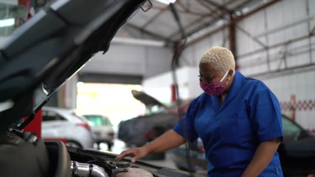 auto mechanic woman working at car repair - automobile industry video stock e b–roll