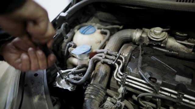 stockvideo's en b-roll-footage met automonteur werken in garage onder de motorkap. reparatie service - motorkap