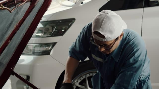 ガレージで働く自動車整備士 - 日曜大工点の映像素材/bロール