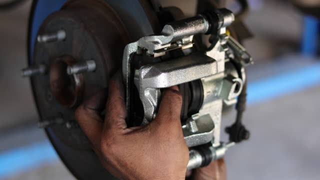auto mechanic working on car wheel brake disc and shoes of lifted automobile at repair service station - calliper stock videos and b-roll footage