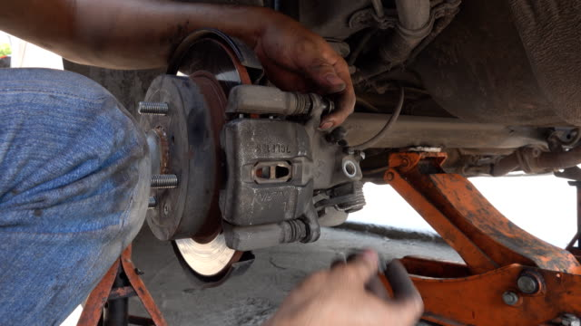 vídeos de stock, filmes e b-roll de mecânico de automóveis, trabalhando no disco de freio de roda de carro em oficina de reparação automóvel - motor