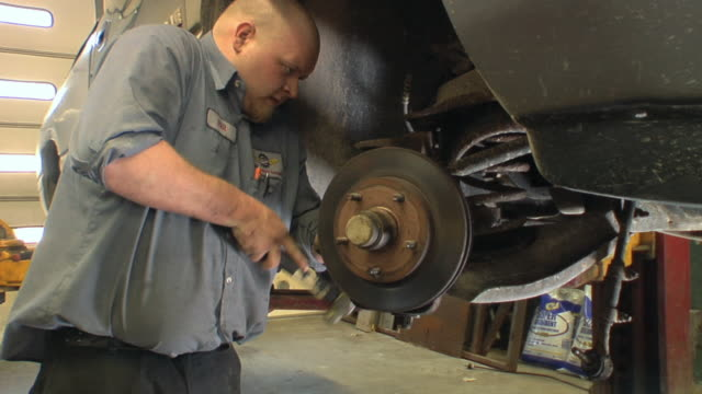 MS Auto mechanic working on vehicle's wheel assembly at auto repair shop / Chelsea, Michigan, USA
