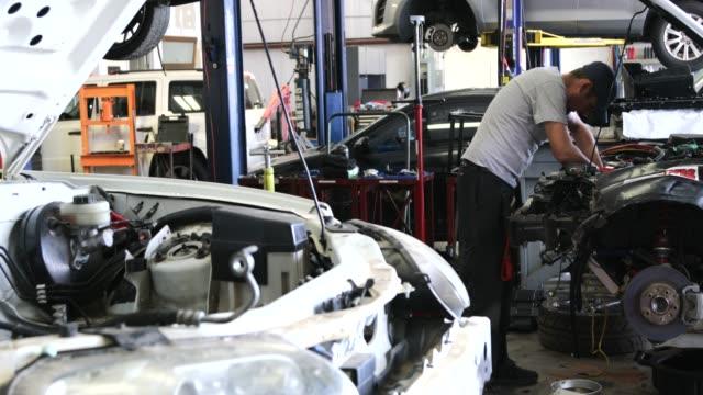 メカニックと自動車修理工場 - 自動車部品点の映像素材/bロール