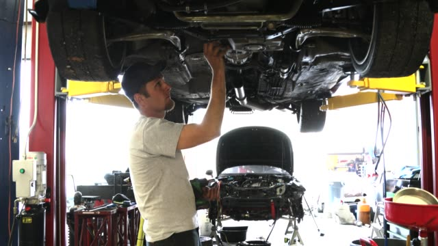 auto repair garage with mechanic - aggiustare video stock e b–roll